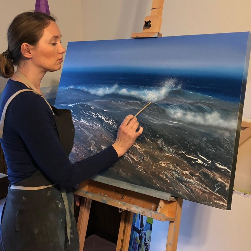 Eva Volf while painting the ocean